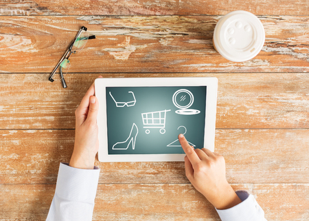 point of sale: fashion, sale, people and technology concept - close up of female hands pointing finger to tablet pc computer with shopping icons on screen Stock Photo