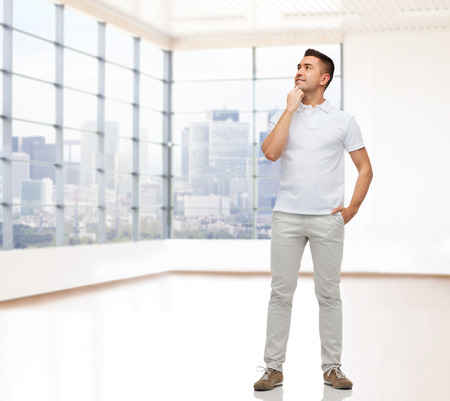 people looking up: real estate, sale, business and people concept - smiling man with hands in pockets looking up over empty apartment or office room with big window and city view background