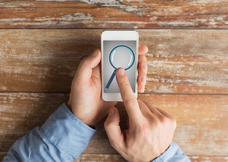 lupas: negocio, la educación, las personas y la tecnología concepto - Cierre de las manos masculinas sosteniendo teléfono inteligente con lupa la imagen en la pantalla de cristal en la mesa