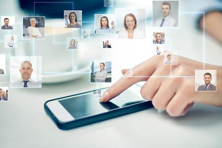 comunicación: negocio, la tecnología, la comunicación global y la gente concepto - cerca de la mano de la mujer con el teléfono inteligente y los iconos de contacto de proyección