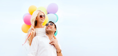 couple in love: summer holidays, celebration and dating concept - couple with colorful balloons