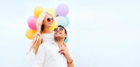 pareja abrazada: vacaciones de verano, la celebración y citas concepto - Pareja con globos de colores Foto de archivo