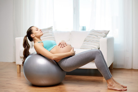 pregnant exercise: pregnancy, sport, fitness, people and healthy lifestyle concept - happy pregnant woman exercising on fitball at home