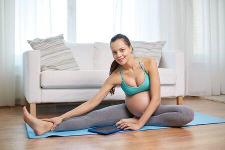 piernas: el embarazo, el deporte, la gente y la tecnolog�a concepto - mujer embarazada feliz con el ordenador Tablet PC ejercicio y extiende la pierna en la estera en casa