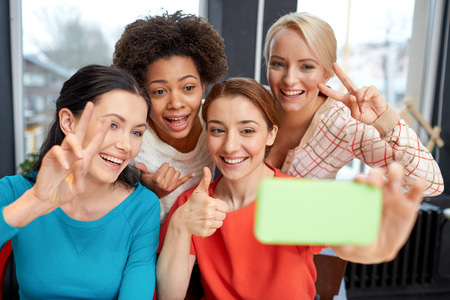 women friendship: people, leisure, friendship, gesture and technology concept - happy young women taking selfie with smartphone and showing victory gesture