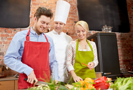 table knife: cooking class, culinary, food and people concept - happy couple and male chef cook cooking in kitchen