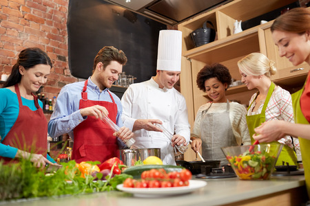 cooking class, culinary, food and people concept - happy group of friends and male chef cook cooking in kitchen Standard-Bild