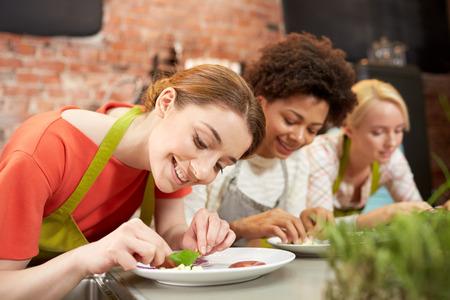 mujeres cocinando: cocinar clase, la amistad, la comida y la gente concepto - mujeres felices de cocina y platos de decoración con los platos en la cocina