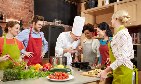 preparing food: cooking class, culinary, food and people concept - happy group of friends and male chef cook cooking in kitchen Stock Photo