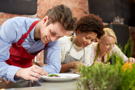 food stuff: cooking class, friendship, food and people concept - happy women cooking and decorating plates with dishes in kitchen