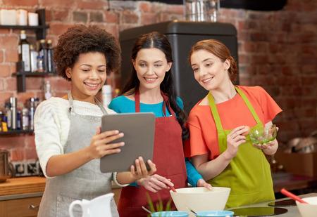 Cooking Class, l'amicizia, il cibo, la tecnologia e le persone concetto - donne felici con il computer tablet pc in cucina Archivio Fotografico - 39597154