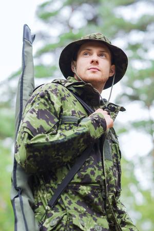 fusil de chasse: la chasse, la guerre, l'armée et le peuple notion - jeune soldat, ranger ou le chasseur avec un pistolet marchant dans la forêt