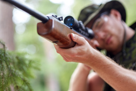 hunting rifle: hunting, war, army and people concept - young soldier, ranger or hunter with gun walking in forest