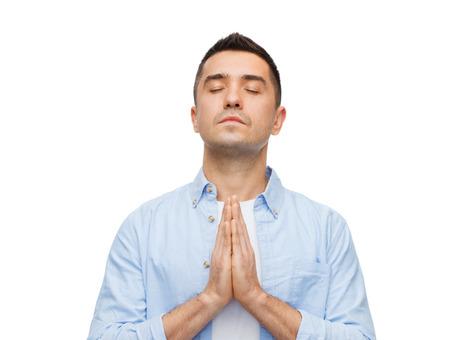 hombre orando: la fe en Dios, la religión y la gente concepto - hombre feliz con los ojos cerrados rezando Foto de archivo