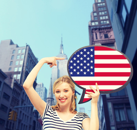english girl: education, foreign language, english, people and communication concept - smiling woman holding text bubble of american flag Stock Photo