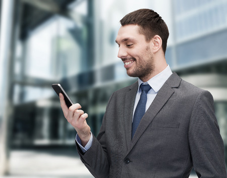 mobile sms: business, technology, internet and education concept - friendly young smiling businessman with smartphone