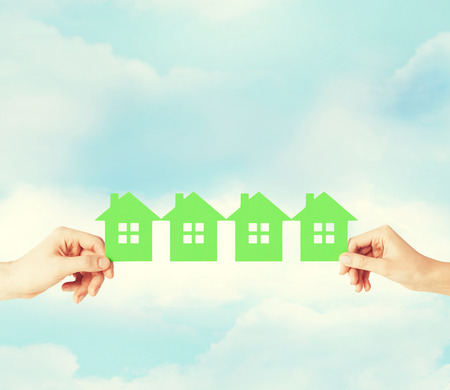real estate and family home concept - closeup picture of male and female hands holding many green paper houses Stock Photo