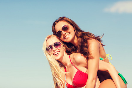 summer vacation, holidays, travel, friendship and people concept - two smiling young women on beach photo