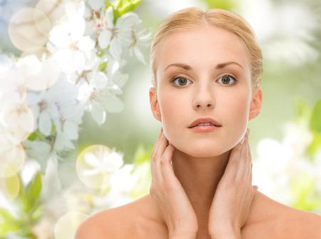 schoonheid, mensen, de zomer, de lente en gezondheid concept - mooie jonge vrouw aan te raken haar nek over groene bloeiende tuin achtergrond Stockfoto