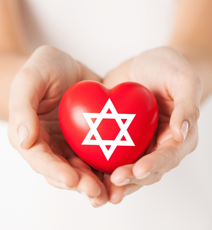 religion, christianity and charity concept - female hands holding red heart with star of david symbol photo