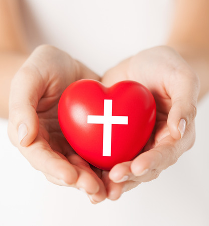 christian community: religion, christianity and charity concept - female hands holding red heart with christian cross symbol