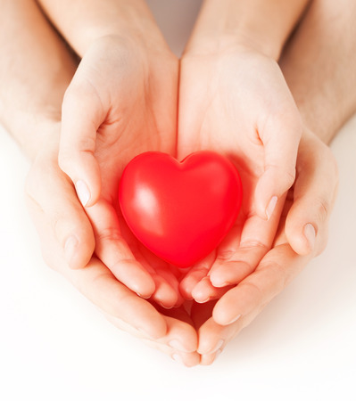 cardiac care: health, love and relationships concept - closeup of couple hands with big red heart