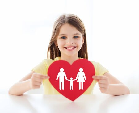 love, home, happiness and adoption concept - smiling little girl with red heart and family picture at home photo
