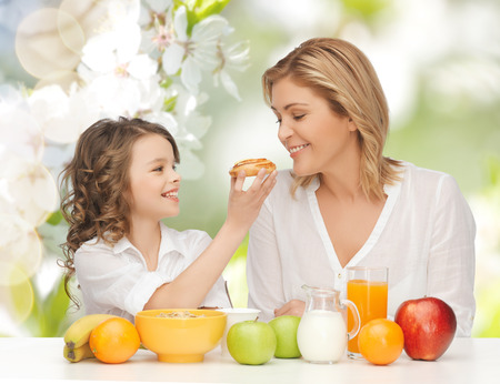 over eating: people, healthy lifestyle, family and food concept - happy mother and daughter eating healthy breakfast over green summer garden background