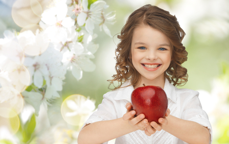 girl apple: people, children, healthy eating and food concept- happy girl holding red apple over summer or spring garden background Stock Photo