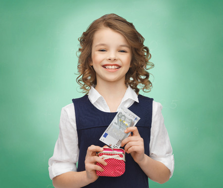 finance girl: finances, childhood, school, people and education concept - happy little girl with purse and paper euro money over green chalk board background Stock Photo