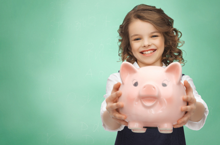 finance girl: people, money, finances and savings concept - happy girl holding piggy bank over green chalk board background Stock Photo