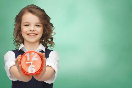 punctuality: la gente, la infancia, el tiempo y el concepto de puntualidad - ni�a feliz con reloj de alarma sobre fondo verde tablero de tiza