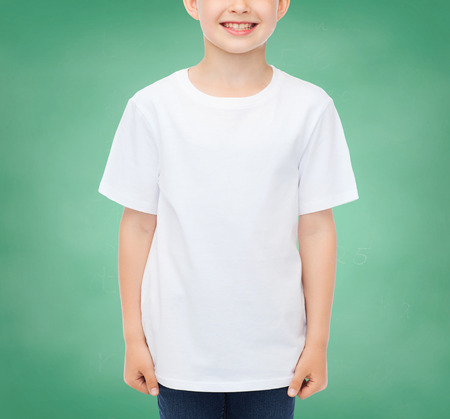 pre teen boy: school, education, advertising, people and childhood concept - smiling little boy in white blank t-shirt over green chalk board background Stock Photo