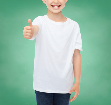 pre approval: school, education, advertising, people and childhood concept - close up of smiling little boy in white blank t-shirt showing thumbs up over green chalk board background