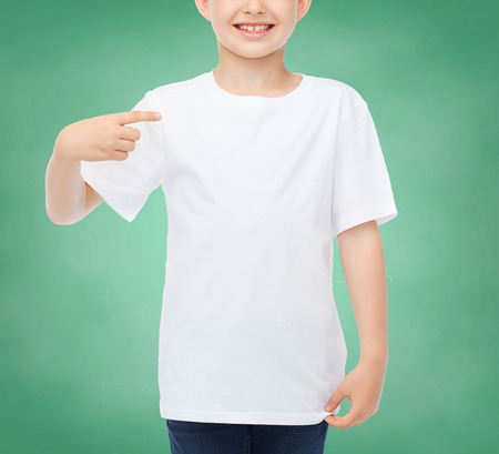 pre teen boys: school, education, advertising, people and childhood concept - smiling little boy in white blank t-shirt pointing finger at himself over green chalk board background