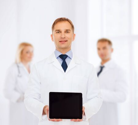 medics: medicine, advertisement and teamwork concept - smiling male doctor showing tablet pc computer screen over group of medics