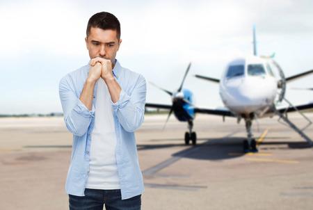 ansiedad: fobia, el miedo, la tristeza y el concepto de la gente - hombre infeliz pensando en avión en el fondo de la pista Foto de archivo