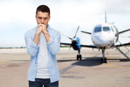 man flying: phobia, fear, sorrow and people concept - unhappy man thinking over airplane on runway background