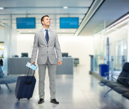 trip over: business trip, traveling, luggage and people concept - happy businessman in suit with travel bag and air ticket over airport background