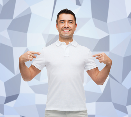 happiness, advertisement, fashion, gesture and people concept - smiling man in t-shirt pointing fingers on himself over gray graphic low poly background photo