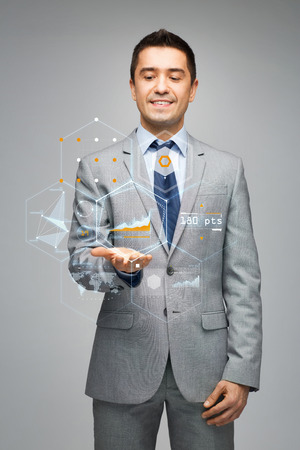 business, people, technology and statistics concept - happy businessman in suit showing virtual screens with charts over gray background photo