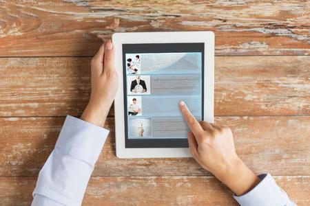ビジネス、教育、人々、インターネットと技術の概念 - タブレット pc コンピューター画面とコーヒー カップ食卓上のウェブページの記事を指を指し