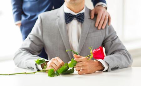 sexo: gente, celebración, la homosexualidad, el matrimonio entre personas del mismo sexo y el amor concepto - cerca de la pareja gay masculina con flores rosa roja que pone la mano en el hombro