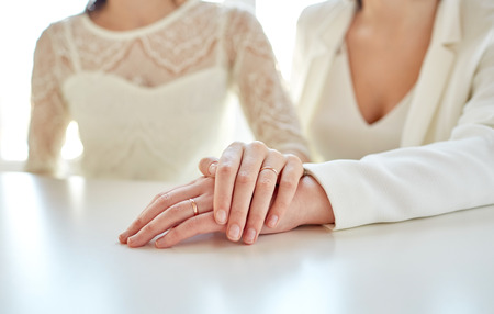 same sex: people, homosexuality, same-sex marriage and love concept - close up of happy married lesbian couple hugging