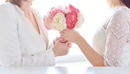 homosexual sex: people, homosexuality, same-sex marriage and love concept - close up of happy married lesbian couple with flower bunch
