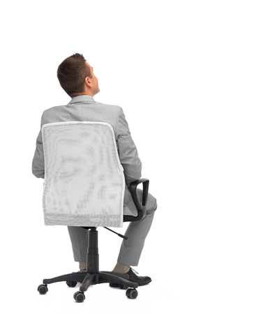 view of an elegant office: business, people, furniture, rear view and office concept - businessman sitting in office chair from back Stock Photo