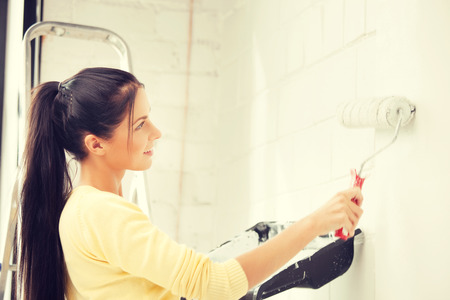 and painting: bright picture of lovely housewife painting at home Stock Photo