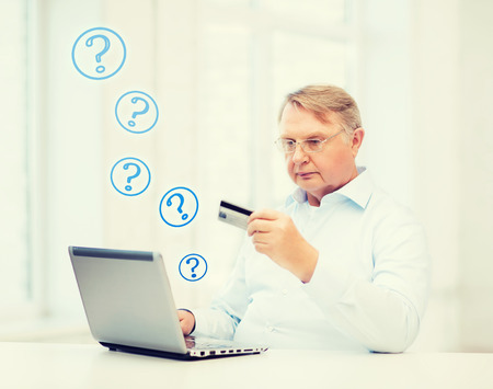 buying questions: business, online banking, internet shopping and oldness concept - smiling old man with laptop computer and credit card at home