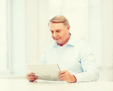 oldness: oldness, news, leisure and happiness concept - old man at home reading newspaper