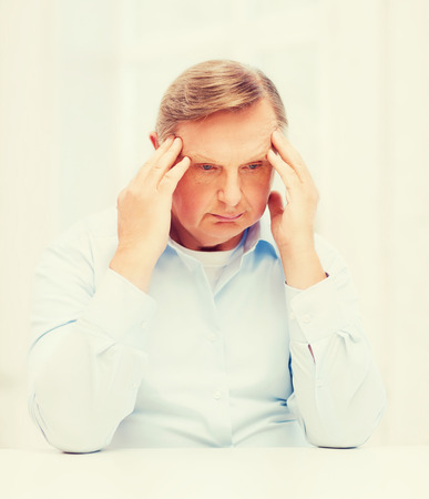 oldness: oldness, business and people concept - stressed old man holding head at home